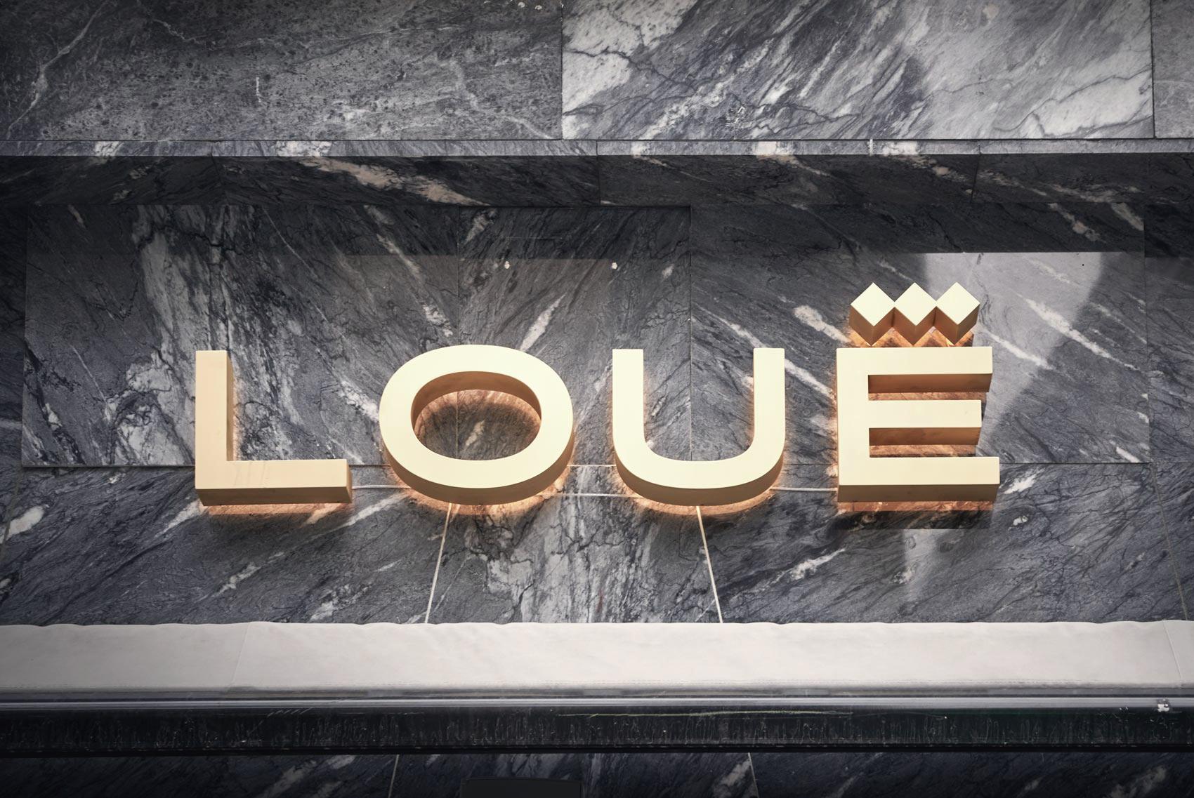 Logo de la tienda de moda de lujo de segunda mano Louë de Madrid en la fachada